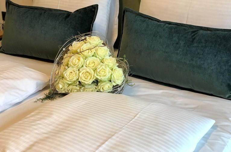 hotel bed with porta nova white naomi eart shaped bouquet